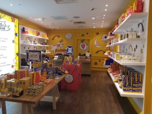 Photograph of the interior of the L'OCCITANE Pop-Up Shop in Las Vegas featuring yellow walls and shelves of skincare, body care, and other beauty products.
