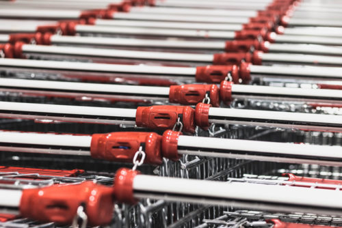 Photo image of two rows of metal shopping carts, with the photo focused specifically on the red and white handles, used as a featured image for a blog post about T.J.Maxx opening a new Las Vegas store.