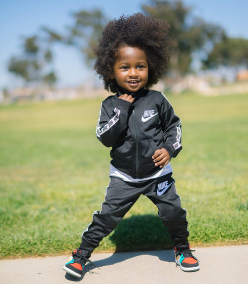 A photograph of an adorable toddler child modeling a Nike brand track suit outdoors at a park.