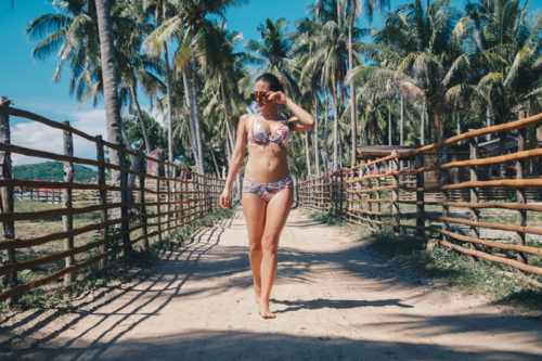 Photograph of a woman in a bikini walking down a dirt road and surrounded by palm trees. This photo is the featured image for a blog post about summer survival products.