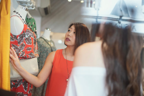 A photograph taken from outside of a store window, looking in on two women touching and staring at a piece of clothing on a hanger. The image is used as a featured image for a blog post about a job where one would get paid to shop.