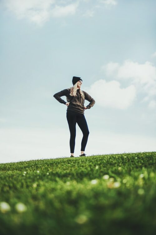 A photo of a woman wearing sneakers, leggings, a sweatshirt, and a knit hat. She is standing atop a grassy hill with her hands on her hips as though she just walked up that hill.