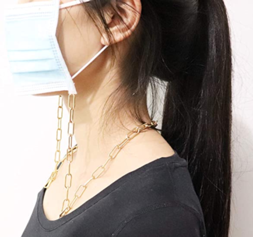 A product shot of a face mask chain connected to a disposable face mask and worn by a female model.
