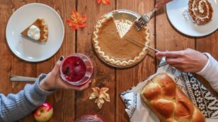 An overhead photograph of a pumpkin pie in the center of a table while one person's hand holds a glass of cranberry drink and another person's hands are cutting into the pie.