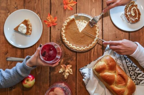 A photograph taken overhead of a table with a pumpkin pie in the center, a cut piece set on a white plate, and a loaf of handmade bread, while one person's hand is holding a cranberry drink and another person's hands are cutting out a slice of pie from the pumpkin pie.