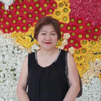 "A photo of Bernadine Racoma, the author of the blog post ""4 Different Things That Make Laminate Floors a Great Investment."" She is wearing a black shirt and standing in front of a wall covered in bright flowers."