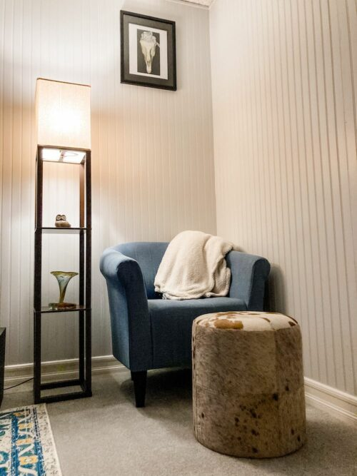 This is a photograph of how I decided to decorate my corner, now complete with the Marlee club chair in blue from Pier 1 Imports, the brown spotted cow hide ottoman from Lamps Plus, the shelf floor lamp from Target, which is turned on in the photo, and a framed print of Georgia O'Keeffe's Horse's Skull with White Rose displayed on the wall. There is a faux shearling blanket draped on the back of the chair. On the shelves of the lamp, there is a small owl figurine on the top shelf and a vintage glass vase on the second shelf beneath it.