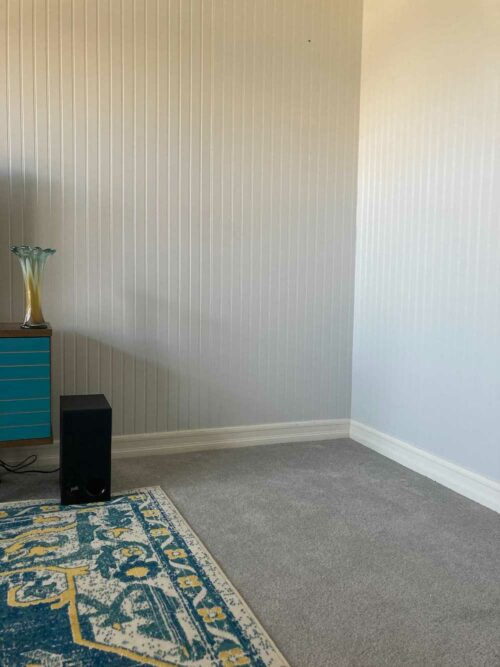 This is a photograph of the empty corner of my living room. The walls are gray paneled. There is a white floor board. There is carpet, which is gray, too. A portion of my blue, yellow, and cream colored patterned carpet is visible, as well as a portion of my entertainment console, which is also blue with brown. The bass speaker from my audio set and a vintage vase that sits on the corner of console are also visible.