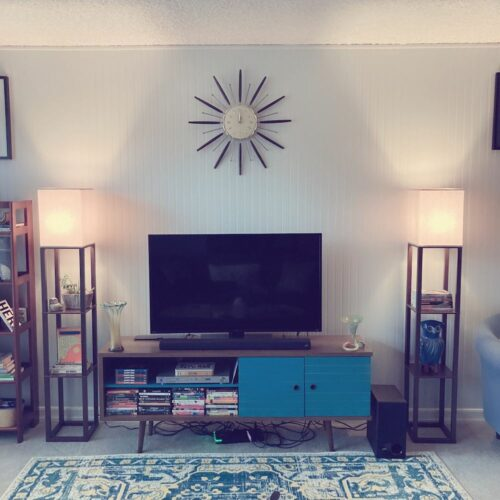 This is a photograph of the TV area of my living room. In this photo, you can see my blue and brown, retro modern style entertainment console with my TV sitting on top. On either side of the console, you can view my two brown shelf floor lamps, which are turned on, from Target. Above the TV, a vintage starburst clock hangs on the wall. Protruding at the bottom of the photo is my blue and yellow-orange area rug.