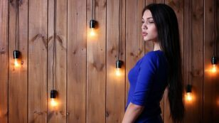 This is a side-view, profile photo of a woman wearing a blue dress. She has long, dark hair and is standing near a wooden paneled wall with hanging light adorning it.