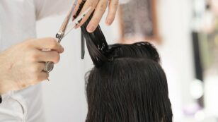 This is a photo of a hairstylist trimming the hair of a woman with brunette hair.