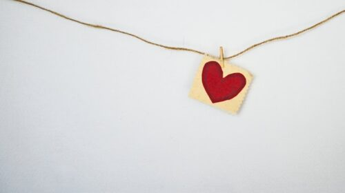 This is a photo of a red heart painted on beige paper and clipped to a piece of twine hanging along a white wall.