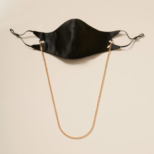 This is a photograph of the Tina Mask in Black Silk With 4mm 18kt Gold Chain from Second Wind.