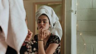 This is a photograph of a woman wearing a floral top and a white towel on her head as she looks in her bathroom mirror and applies beauty product to her lips.