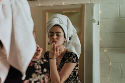 This is a photograph of a woman wearing a floral blouse and a white towel on her head as she looks in the mirror and applies beauty product to her lips.