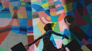 This is a photo of a woman holding shopping bags and leaping with joy, as a colorful, mosaic painted mural sits behind her.