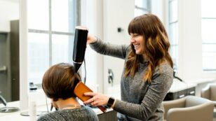 This is a photo of a hair stylist blow drying and styling a woman with short hair.