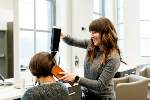 This is a photo of a hair stylist styling a woman's short hair.
