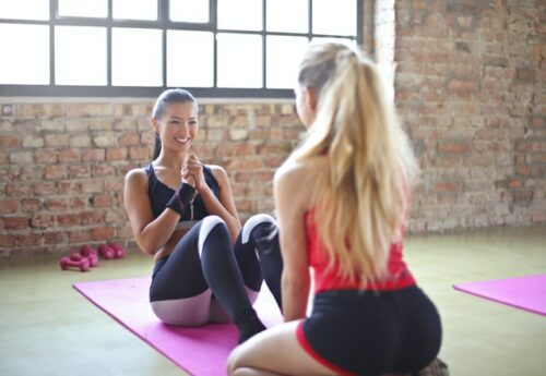 This is a photograph of two women. One is sitting on a yoga mat as though she is about to do a sit-up while the other woman is on her knees holding her feet.
