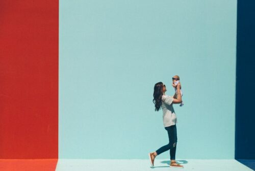 This is a photograph of a mother holding her baby up so they are face to face with an attractive red, light blue, and navy painted wall behind them.