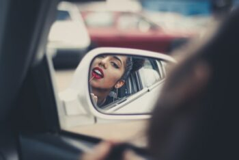 This is an image of a woman sitting in a car, looking into the side mirror and applying lipstick.