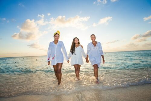 This is an outdoor photo on the beach of three women wearing white dresses holding hands as they walk with the ocean behind them.