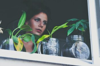 This is a photo of woman looking out her window with three plants sitting on the window sill.