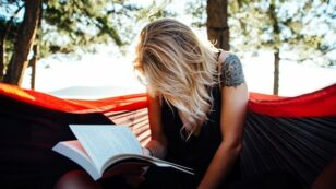 This is a photo of a woman sitting in a hammock reading a book.