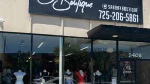 This is an exterior photograph of Sabrak Boutique Las Vegas which shows a sign that displays the phone number, 725-206-5861, and the URL www.sabrakboutique.com.