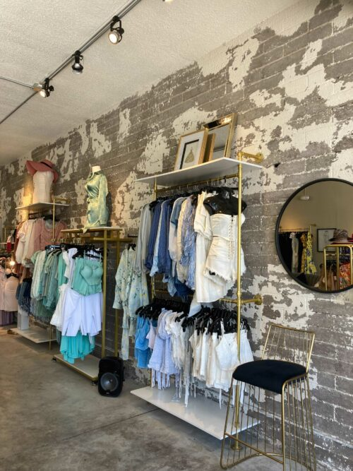 This is an interior image of Sabrak Boutique Las Vegas which shows a stylishly distressed painted wall and clothings racks.