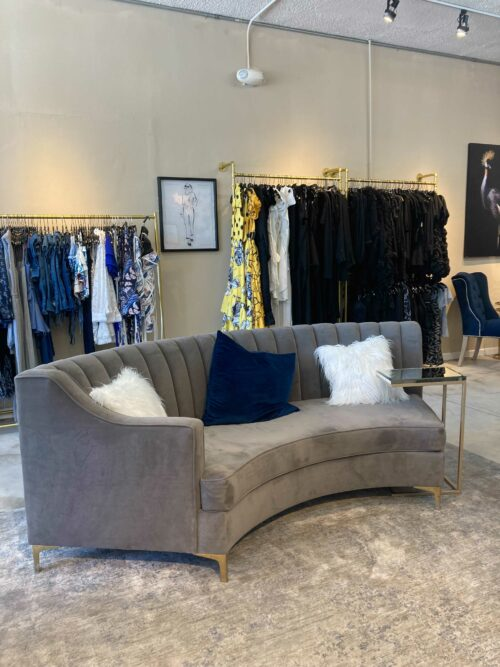 This is an interior photograph of Sabrak Boutique Las Vegas which shows a gray velvet love seat and racks of fashion clothing.