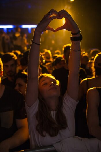 This is a photo of a woman at a live show. Her eyes are closed and she is smiling as her arms are in the air and she makes a heart shape with her hands.