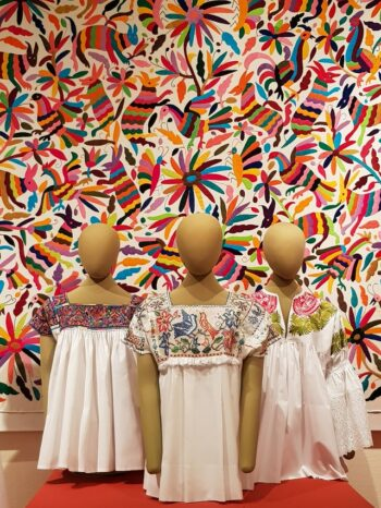 This is a photograph of three mannequins wearing Otomi embroidered bloused with a colorful Otomi embroidered quilt hanging as the backdrop.