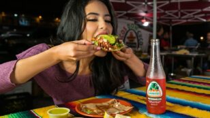 This is a photo of a woman going out alone at a Mexican food restaurant. She is biting into a delicious looking tostada with a bottle of watermelon Jarritos on the table beside her.