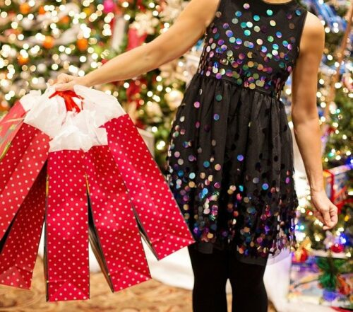 This is a photograph of a woman in a black, sparkly dress holding five red gift bags. There is lit Christmas tree behind her.